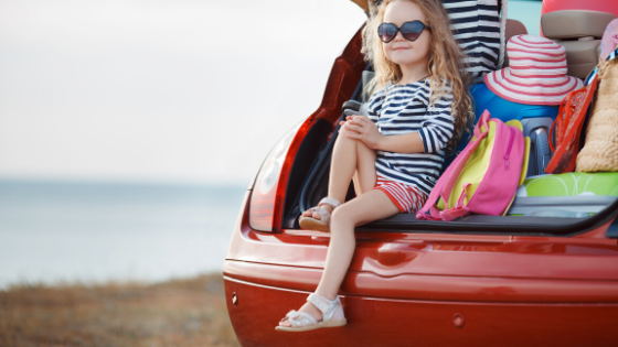 girl on vacation sitting in packed car